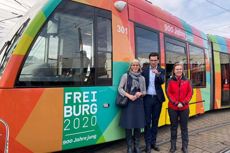 3 Personen vor Straßenbahn in Freiburg