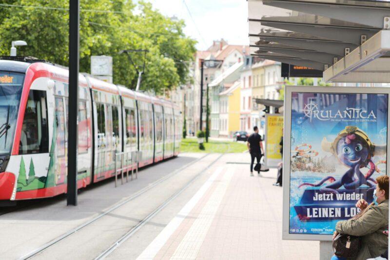 Foto zu Stellenangebot: Straßenbahn mit Rothaus-Werbung und Fahrgastunterstand mit CLP-Plakat Rulantica vom Europa-Park